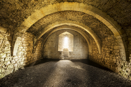 vaulted ceiling: Room inside an old castle with a window cell and archways