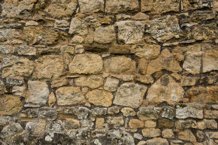 Old ancient rough cobblestone wall background texture