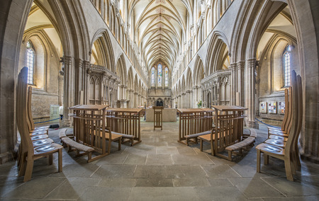 vaulted ceiling: Elegant symmetrical church interior with a long nave with gothic arches in a vaulted ceiling, pews and high backed chairs with a light white and beige decor. Wells Cathedral, Somerset, UK