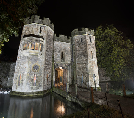 Bishops Palace Gatehouse in Wells, Somerset, UK illuminated at Night with the drawbridge out