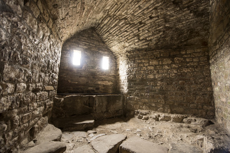 evocative: Room inside an old castle with a window cell and archways