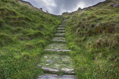Old ancient rocky cobblestone steps going up a grass hill photo