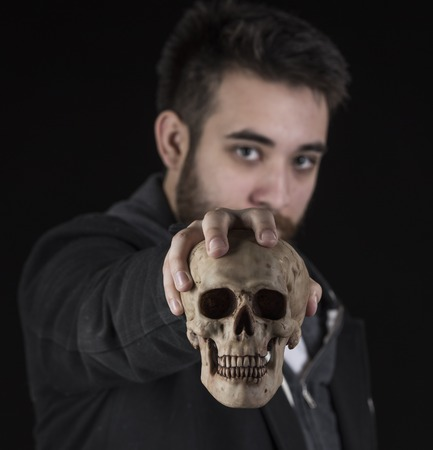parentage: Gorgeous Young Man Wearing Black Jacket Shirt Holding Skull While Looking at the Camera. Isolated on Black Background.