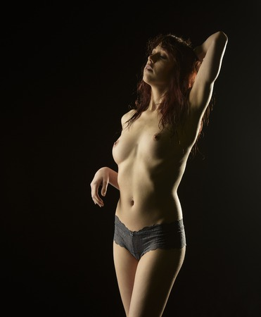 naked belly: Portrait of Sensual Topless Young Woman Posing in Gray Panties with One Arm Up, Facing Left Frame. Isolated on Black Background.