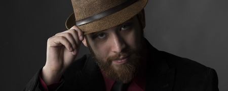 observant: Close up Serious Goatee Young Man Face Wearing Brown Hat While Looking at the Camera on Gray Background.