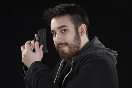 operative: Close up Handsome Goatee Young Man Wearing Black Jacket Holding Small Gun in Side View. Isolated on Black Background.