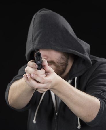 druggie: Close up Giovane serio in nero Hood holding pistola su sfondo nero. Sottolineando Crime Concept.