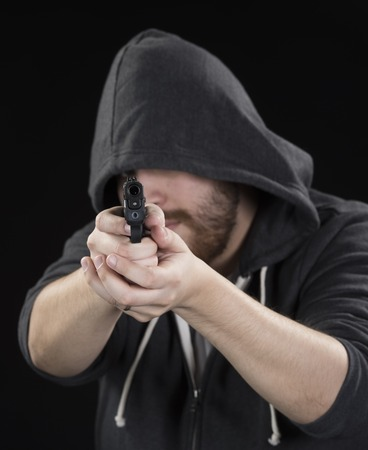 druggie: Close up Serious Young Man in Black Hood Holding Gun on Black Background. Emphasizing Crime Concept.