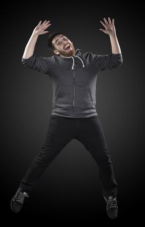 gambe aperte: Figura intera bel tiro di uomo giovane che indossa la camicia casual in Wacky Pose, sottolineando le mani e le gambe aperte su Gradiente Sfondo grigio.