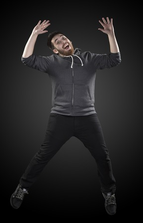 high spirited: Full Length Shot of Handsome Young Man Wearing Casual Shirt in Wacky Pose, Emphasizing Hands up and Open Legs on Gradient Gray Background. Stock Photo