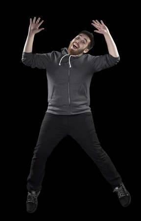 Full Length Shot of Happy Young Man in Casual Attire Doing Wacky Pose While Looking at the Camera on Black Background photo