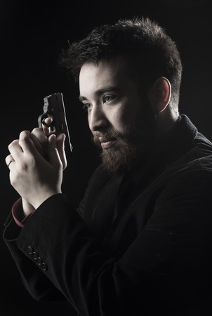 felon: Close up Goatee Young Man Wearing Black Suit Holding Small Gun While Looking Left Side. Isolated on Black.