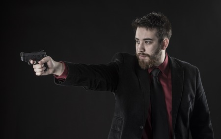 operative: Half Body Shot of Goatee Young Man in Black Suit Aiming a Small Gun in Side View. Isolated on Black Background. Stock Photo