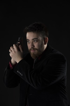 operative: Half Body Shot of Gorgeous Goatee Man Wearing Black Suit Holding Small Black Gun. Isolated on Black Background.