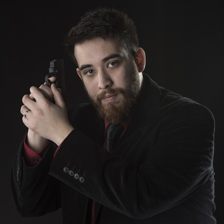 operative: Close up Young Goatee Agent Wearing Black Suit Holding Pistol While Looking at the Camera. Isolated on Black.