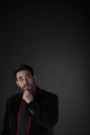 goatee: Handsome Goatee Thoughtful Businessman in Black Suit Looking Up with Copy Space on Gray Background. Stock Photo