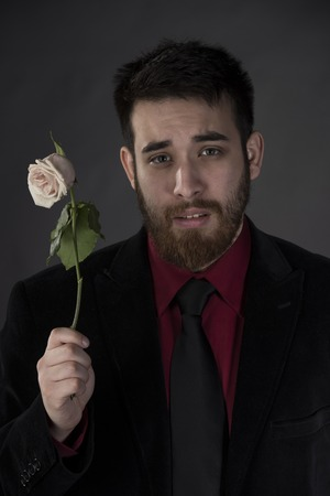 lovelorn: Close up Sad Young Man in Elegant Formal Wear Holding Withered Rose on One Hand While Looking at the Camera. Isolated on Gray Background.