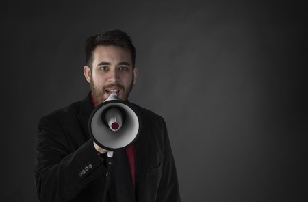 loud: Close up Young Man in Black Suit Speaking Using Megaphone with Copy Space on Side. Captured on Gray Background.