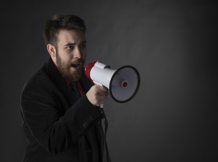 verbal: Conceptual Talking Serious Young Man in Formal Wear Using Megaphone on Gradient Gray Background. Stock Photo
