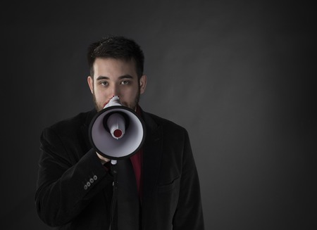 verbal communication: Close up Young Gorgeous Man Wearing Formal Suit Holding Megaphone While Looking at the Camera on Gradient Gray Background.