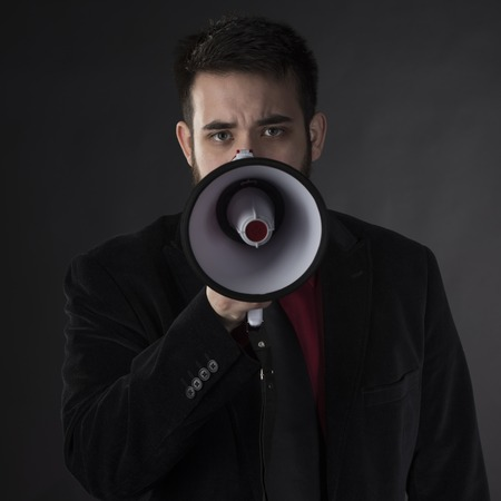 boycott: Close up Serious Young Man in Black Formal Wear Holding Megaphone While Looking at the Camera. Captured on Gray Background.