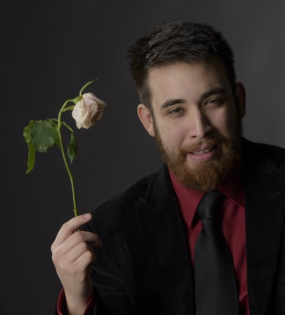 goatee: Close up Smiling Handsome Goatee Man in Formal Attire Holding Withered White Rose While Looking at the Camera. Captured on Gray Background.