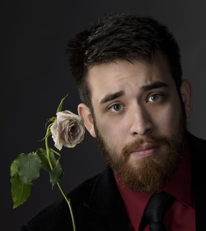 goatee: Close up Good Looking Young Goatee Man with Off White Rose Looking at the Camera. Isolated on Gray Background.