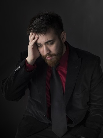 downhearted: Sitting Young Man in Black and Maroon Formal Attire Suffering Headache with Hand on his Head. Captured on Gray Background. Stock Photo