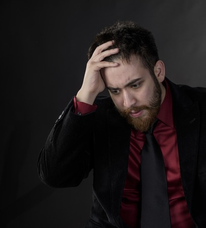 forgetful: Close up Troubled Goatee Young Man in Black and Maroon Formal Wear. Captured on Gray Background. Stock Photo