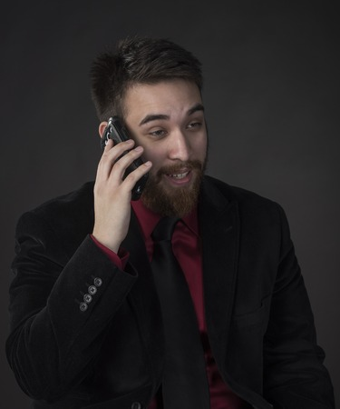 Close up Happy Young Businessman in Black Suit Talking Through Mobile Phone on Gray Background.