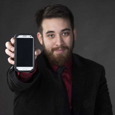 emphasizing: Close up Young Goatee Businessman Showing his Smart Phone While Looking at the Camera. Emphasizing Copy Space on Screen. Isolated on Gray Background. Stock Photo