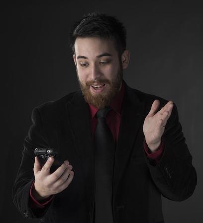 Close up Überraschter junger Geschäftsmann, der sein Handy mit Geöffneter Mund. Auf grauem Hintergrund eingefangen.