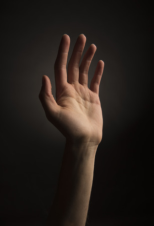 reaching hand: Skinny ectomorph hand reading up on black background