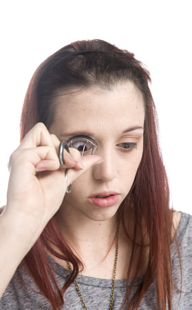 curler: Close Up of Serious Young Teenage Girl Curling Eyelashes with Eyelash Curler with White Background