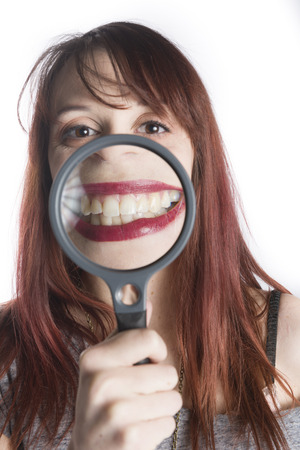 Playful Young Teenage Woman Holding Magnifying Glass in front of Mouth to Enlarge Toothy Smile Stok Fotoğraf - 37925063