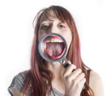 Mujer joven que sostiene la lupa delante de la boca abierta Haciendo boca parezca más grande