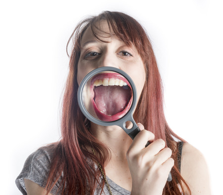 Young Woman Holding Magnifying Glass in front of Open Mouth Making Mouth Look Bigger Stock Photo