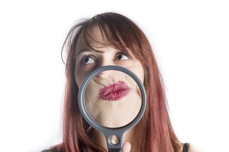 puckered: Perplexed Looking Young Woman with Magnifying Glass in front of Puckered Up Mouth Looking as if Thinking Hard