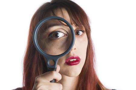 femme policier: Close Up de jeune femme avec des cheveux rouge à travers la recherche Loupe devant les yeux, la recherche d'indices