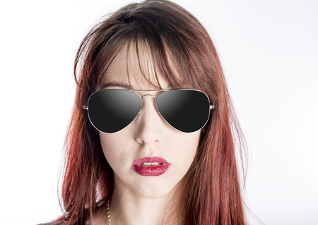 attitude girls: Close Up of Serious Young Woman with Attitude Wearing Aviator Style Sunglasses with Dark Lenses on White Background