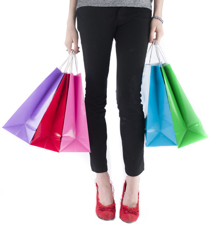 spendthrift: Close Up of Bottom Half of Young Woman Wearing Leggings and Red High Heel Shoes Carrying Colorful Shopping Bags on White Background