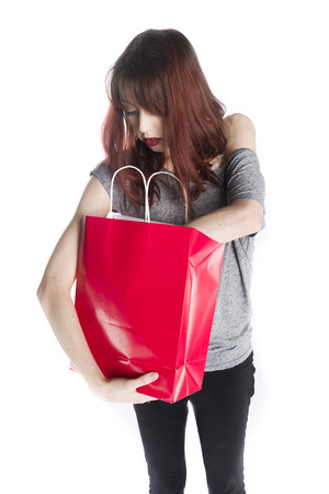 woman searching: Young Woman Looking into Red Shopping Bag as if Searching for Something, Standing in Studio with White Background Stock Photo