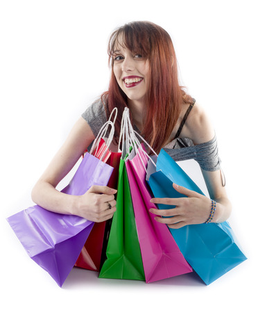 possessive: Smiling Young Teenage Woman with Red Hair Hugging Collection of Five Colorful Shopping Bags on White Background Stock Photo