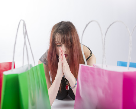 Young Woman with Red Hair Praying with Eyes Closed near Collection of Colorful Shopping Bags