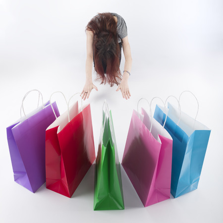 adulation: Woman with Long Hair Bowing on the Floor In Front of Colored Shopping Paper Bags. Isolated on White Background.