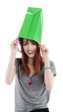 fancy bag: Playful and Smiling Young Teenage Woman with Green Shopping Bag on Head in front of White Background