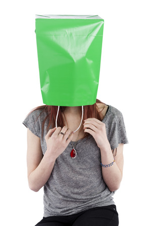 hiding face: Young Playful Teenage Woman Hiding with Green Shopping Bag over Head Obscuring Face and Identity Stock Photo