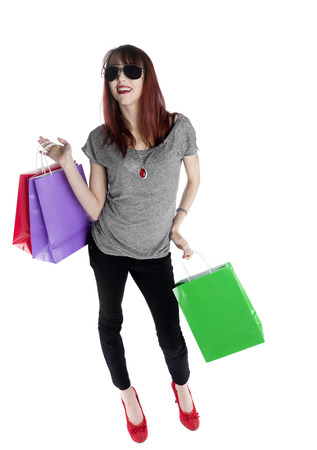 spending full: Full Length Shot of a Happy Young Woman in Trendy Outfit Holding Colored Shopping Bags, Isolated on White Background.