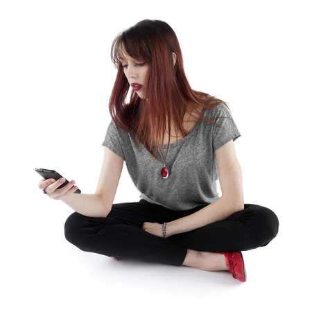 Serious Pretty Young Woman Sitting on the Floor with Legs Crossed While Holding her Mobile Phone, Isolated on White Background. photo