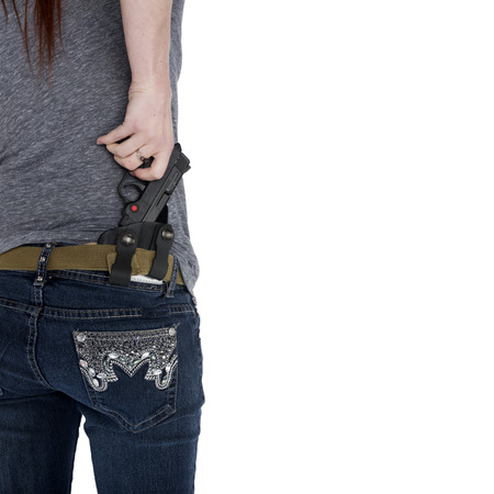 Close up Woman in Casual Clothing Pulling her Hand Gun from her Hip Holster, Isolated on White Background.